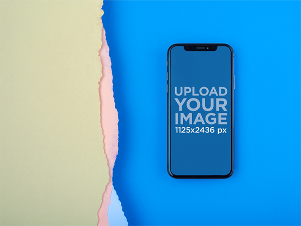 iphonex mockup lying on a blue surface near broken paper